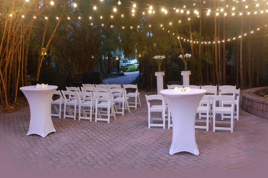 outdoor terrace with lights and white chairs