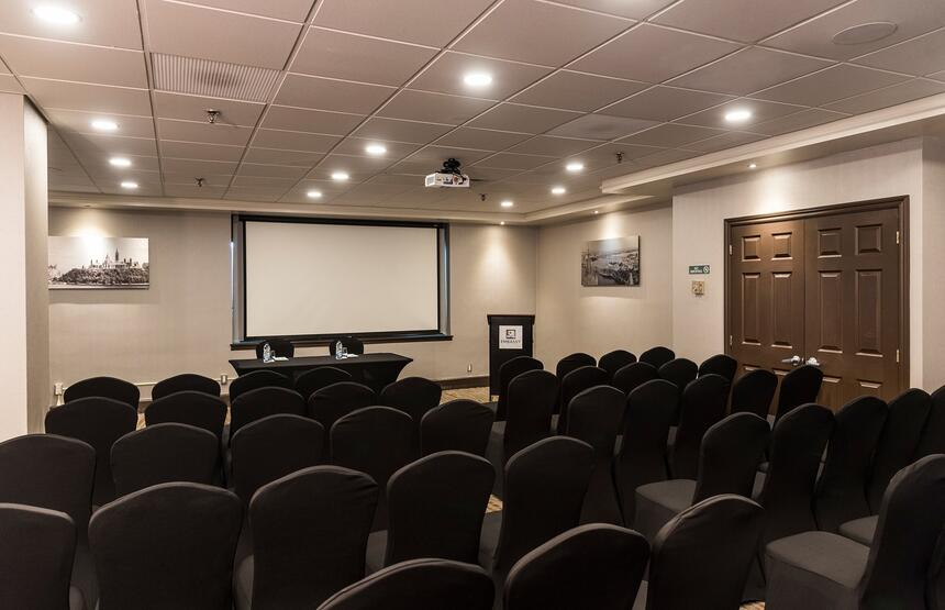 conference room with chairs lined up and projector on wall