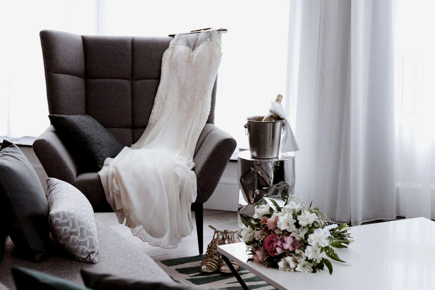 Detail shot of wedding dress on chair with bouquet on nearby tab