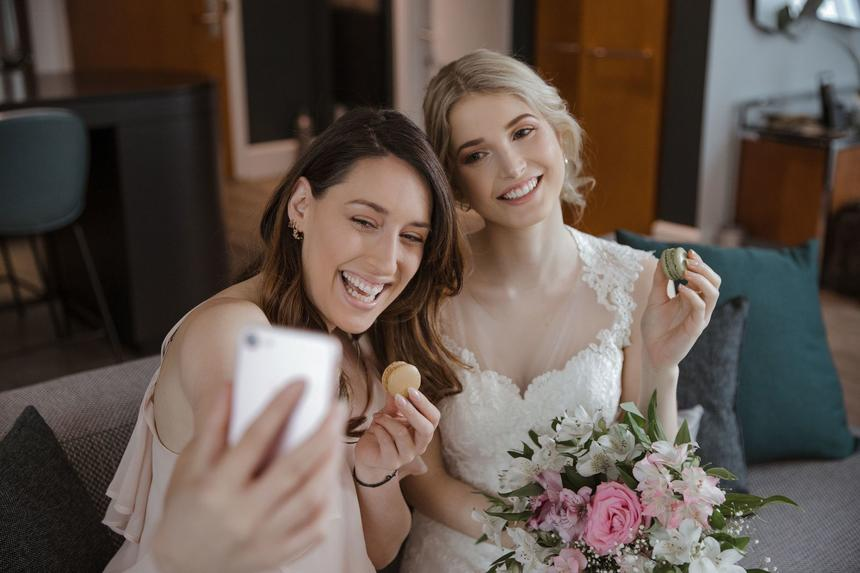 Bride & bridesmaid posing for selfie while eating marcarons
