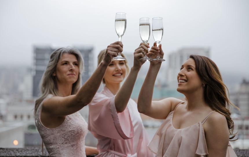 Trio of women clinking glasses of champagne on balcony