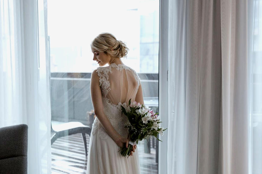 Bride posing in front of window with wedding bouquet