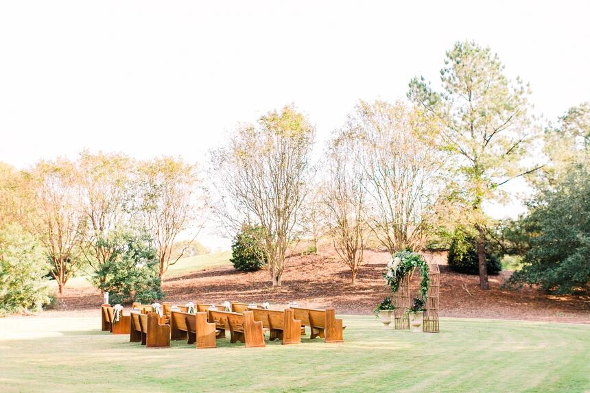 wedding venue in green field with woods in background
