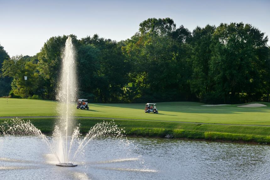 lake and fountain next to golf course