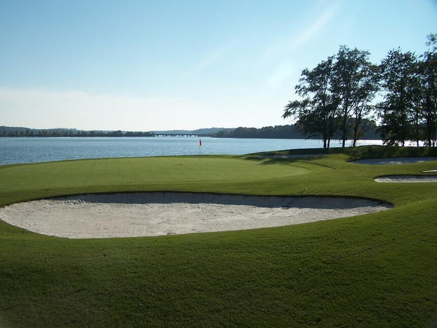 sand pit on golf course with lake in the background