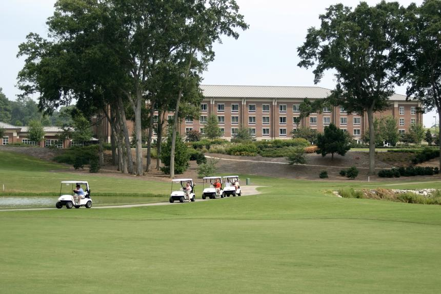 golf carts on golf course with brick building in background