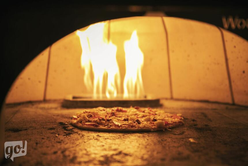 a pizza cooking in a brick oven