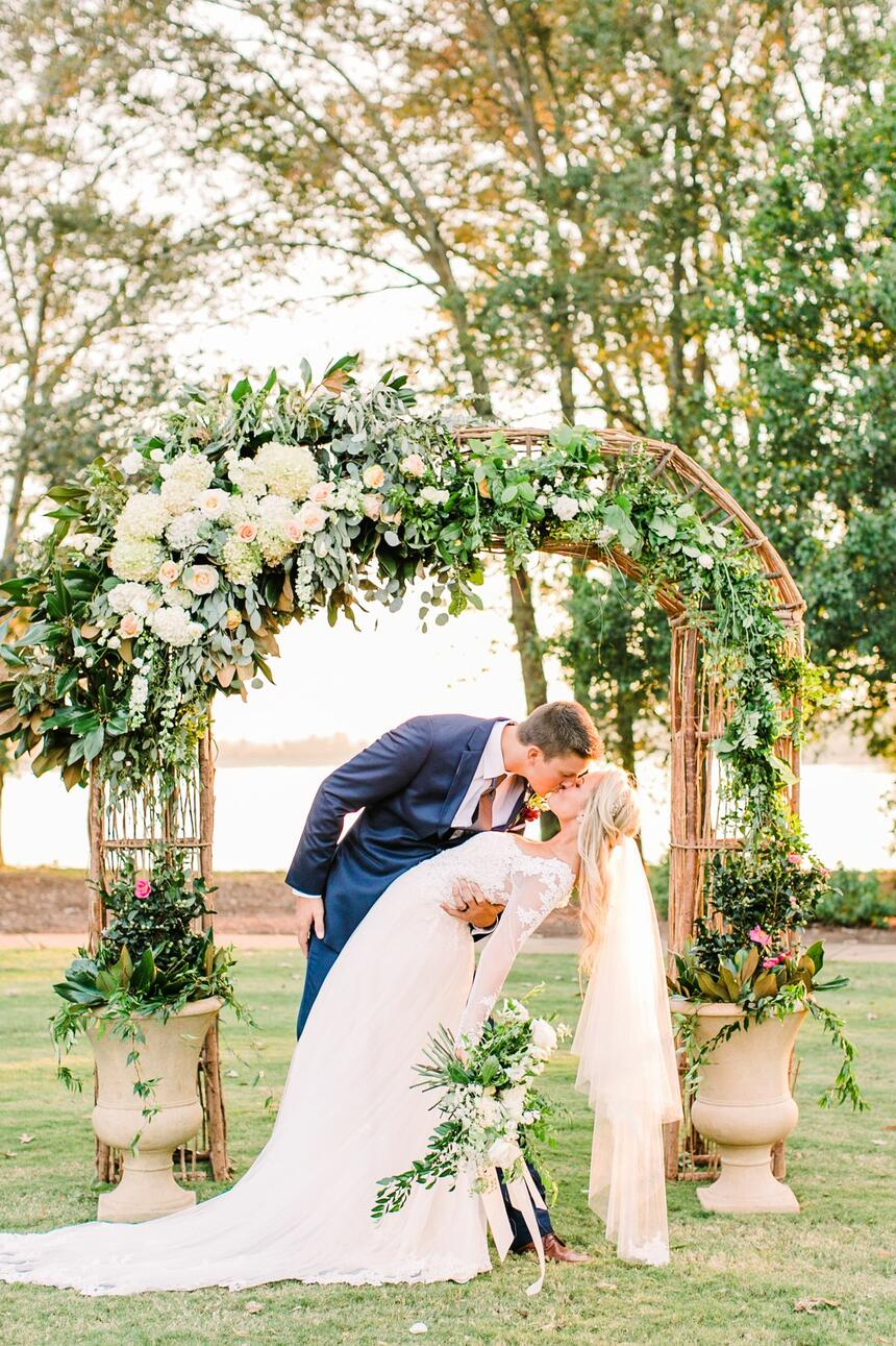 bride and groom kissing at altar