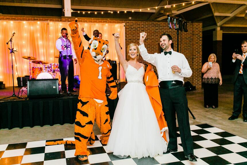 bride and groom celebrating with clemson mascot