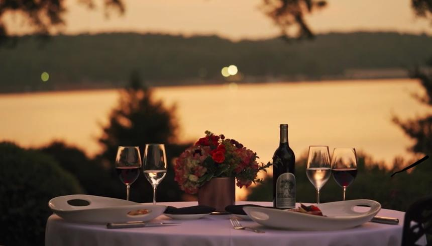 romantic dining table with wine overlooking sunset over lake
