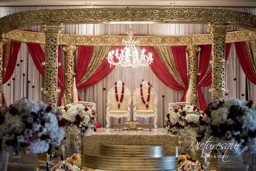 indian wedding altar with white chairs and red curtain draping