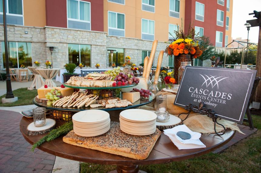 table with cheese platter, plates and napkins