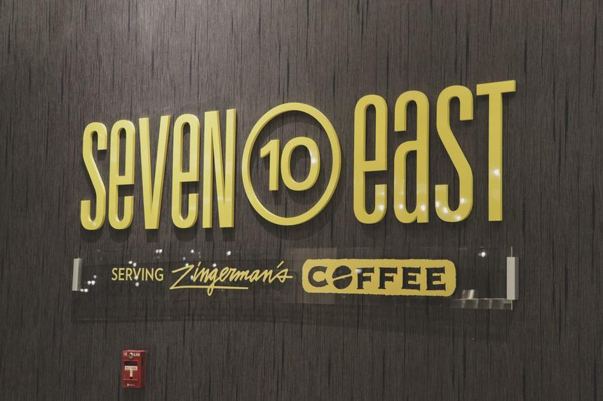 black wall with yellow letters that say seven 10 east coffee