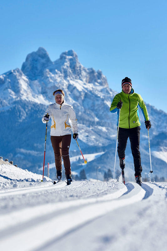 two women skiing with mountain view