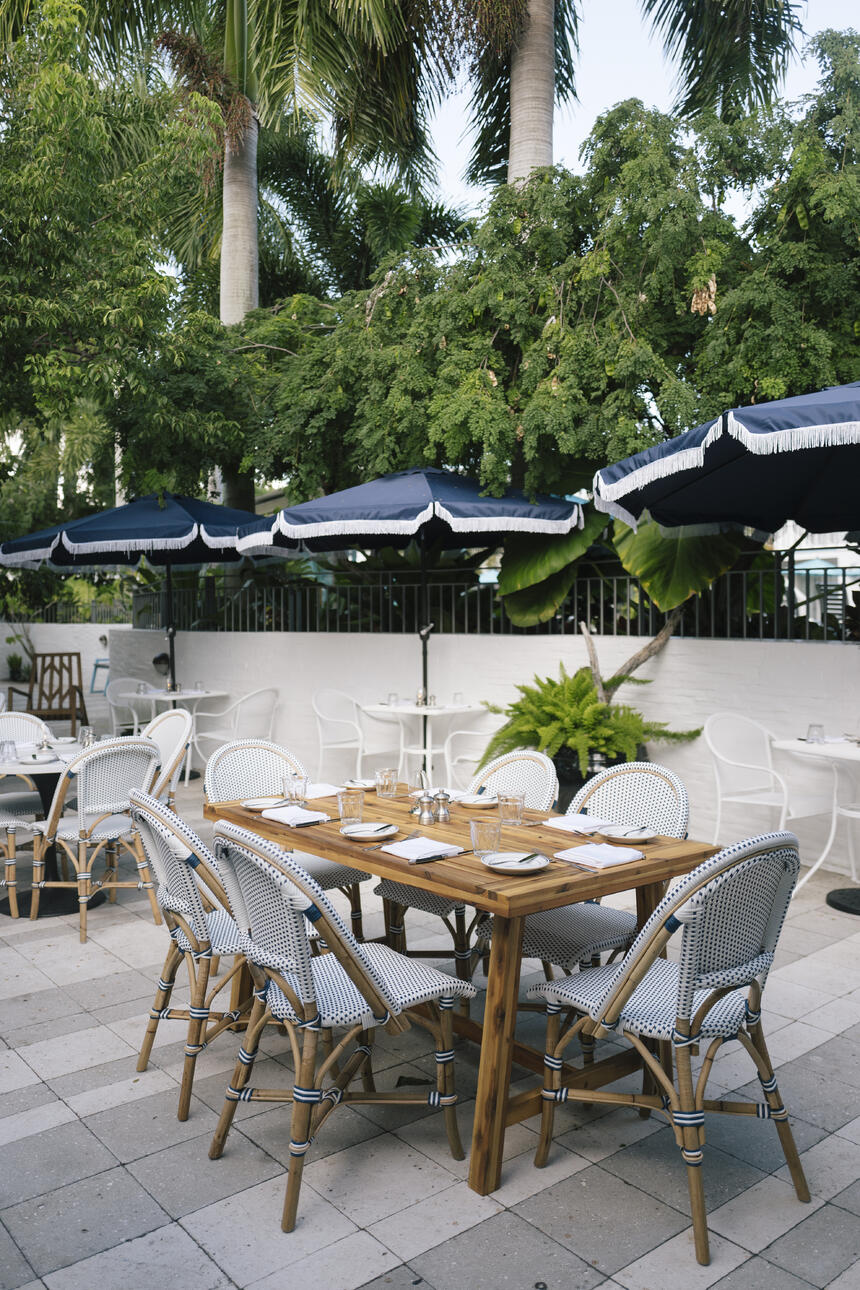 Outdoor restaurant seating area with open navy blue umbrellas
