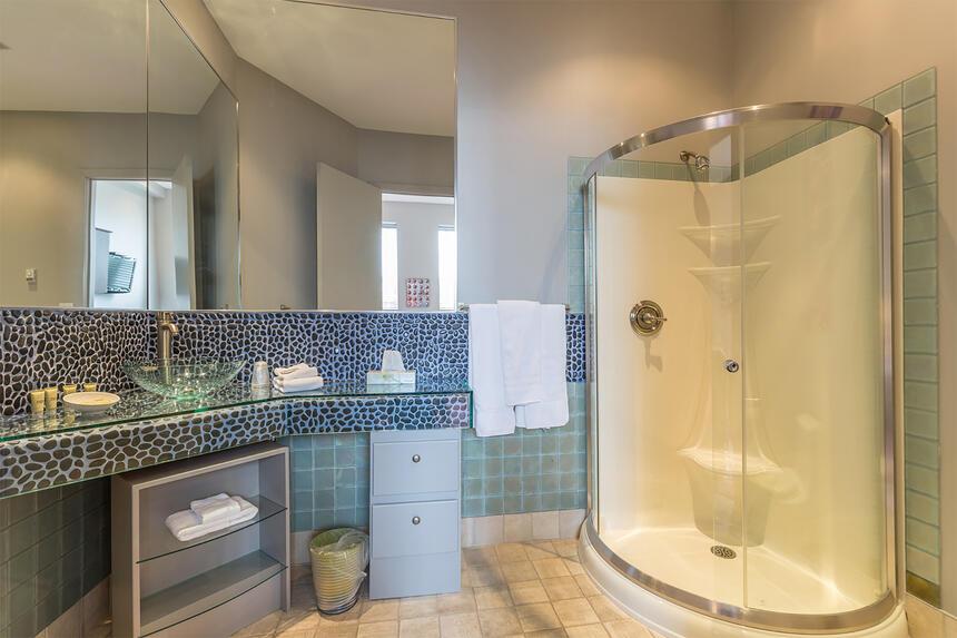 bathroom with rounded corner shower and pebble tile backsplash