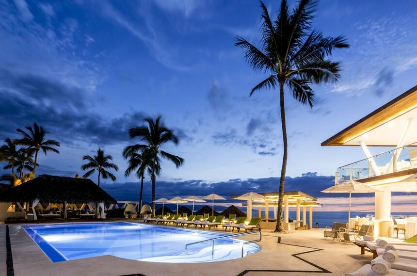 palm trees surround a beachfront pool