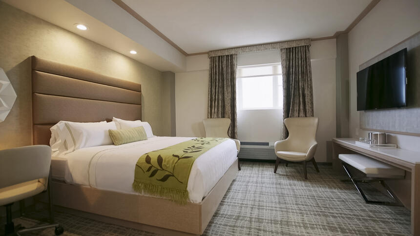 a bed and two chairs in a hotel room