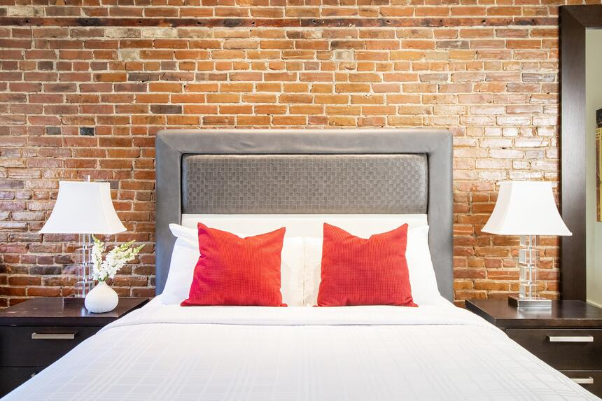 queen bed with two red accent pillows with exposed brick wall