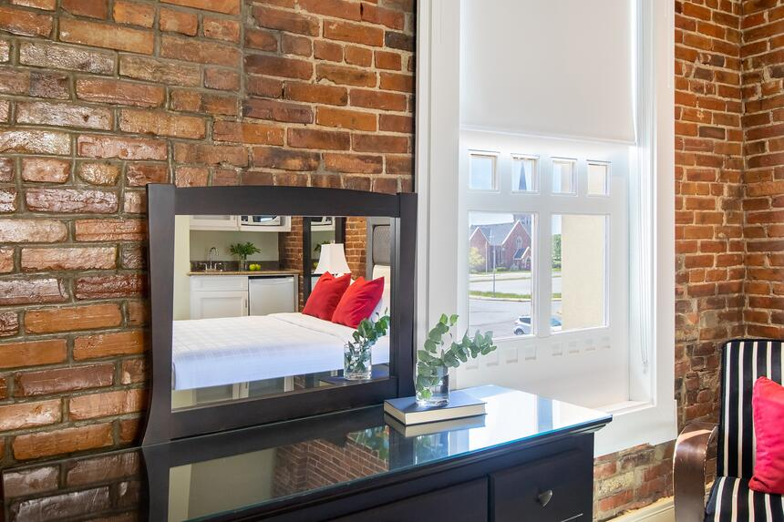 mirrored desk with chair near big window with exposed brick