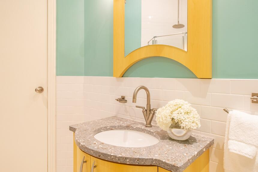 a bright blue bathroom with a yellow trim mirror and sink in sun