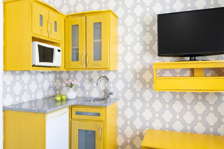 a bright yellow kitchenette with decorative wall paper and a wal