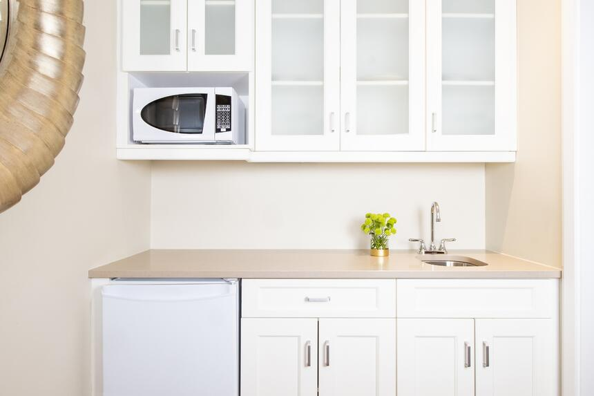 bright white kitchenette with mini fridge, sink and microwave