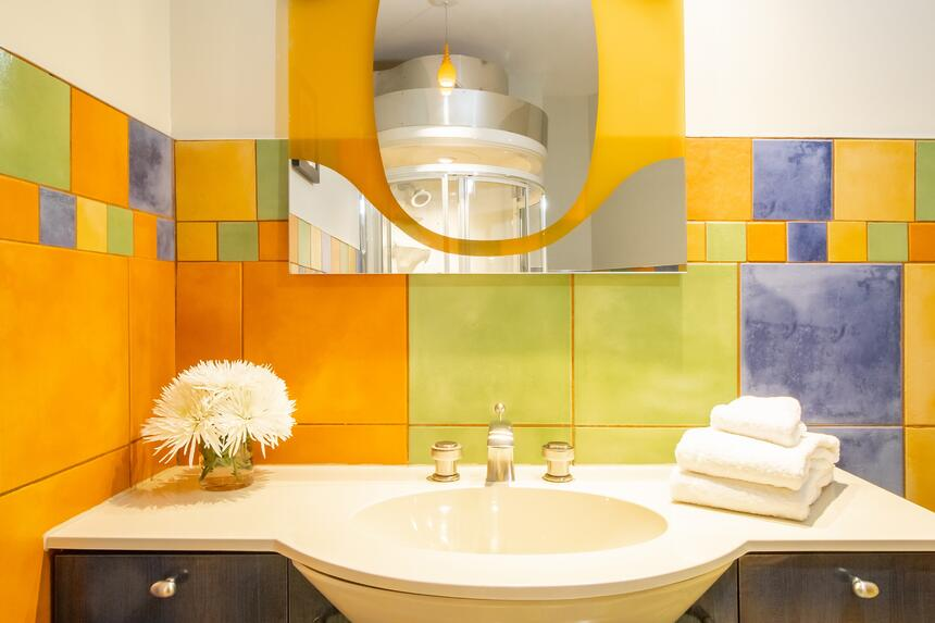 colourful bathroom countertop and tile in brownstone, funky mirr