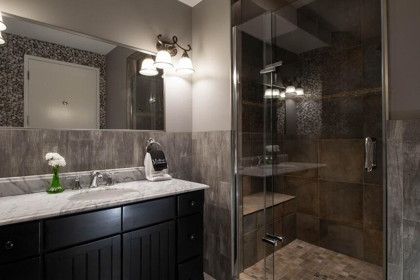bathroom with stone looking glass walk-in shower and grey counte