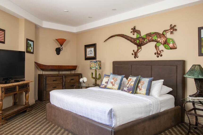 a gecko on the wall behind a king bed in cowboy suite with cactu