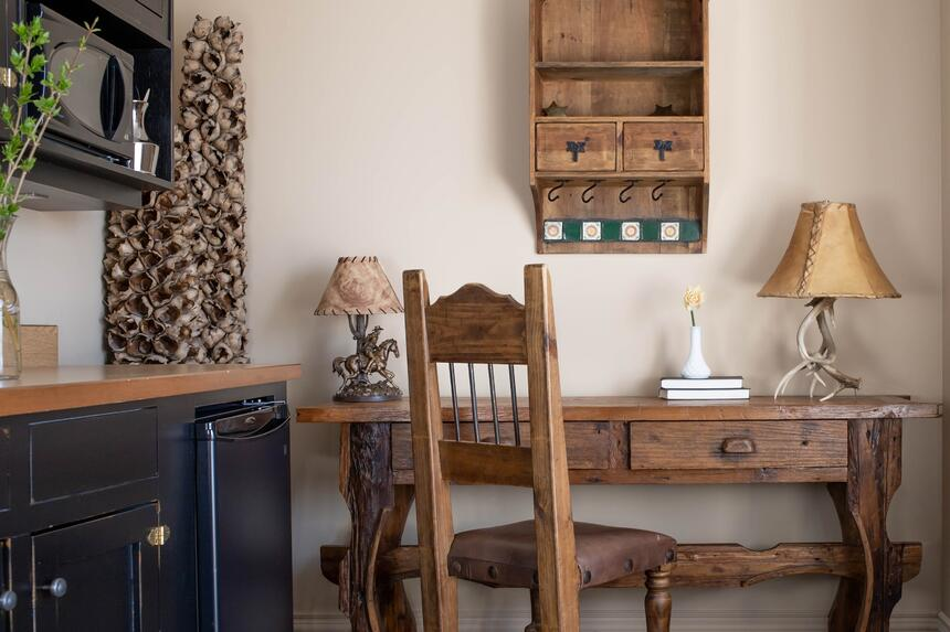wooden chair at a wooden desk with decorative antler lamps