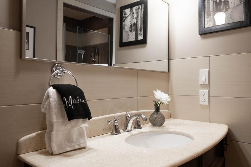 bathroom with sink and mirror and contemporary artwork on walls