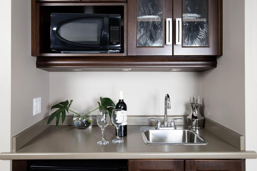 kitchenette with sink and cupboards, microwave and glasses of wi