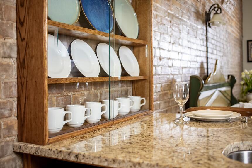 a bar countertop with glassware and plates set up ready for a me