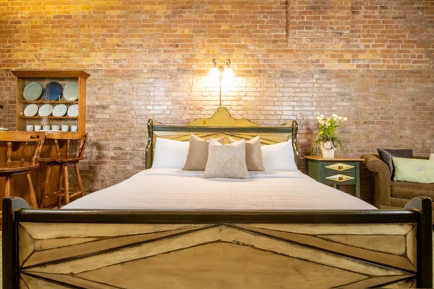 king bed with exposed brick walls and carved wood headboard