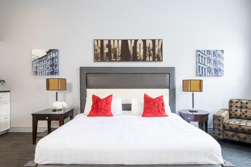 a king bed with matching bedside lamps, art work says new york a
