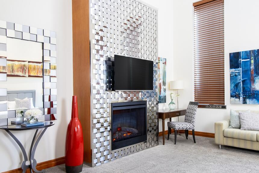 stainless steel woven fireplace with tv mounted above and desk b