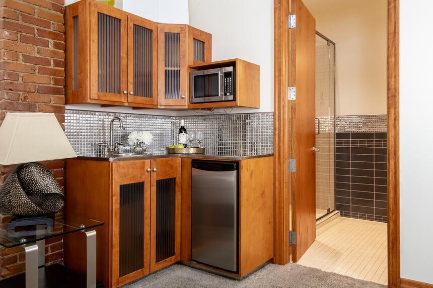 corner kitchenette with stainless backsplash, fridge and microwa