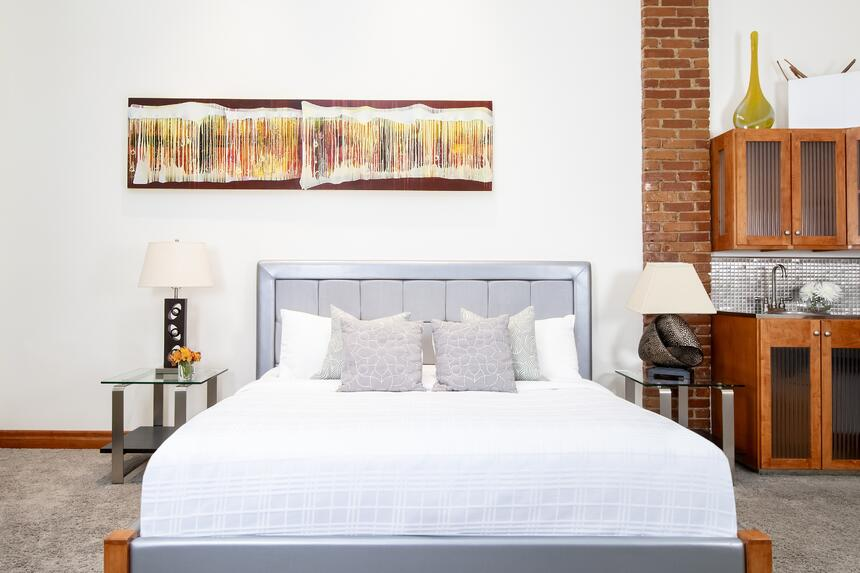 king bed with artwork on wall and exposed brick column behind