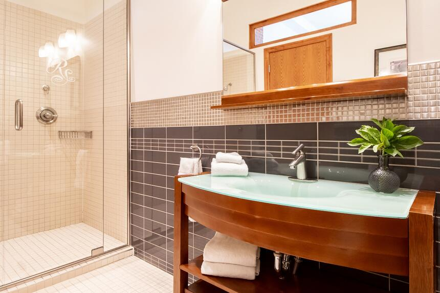 bathroom with mirror and sink with walk in glass shower