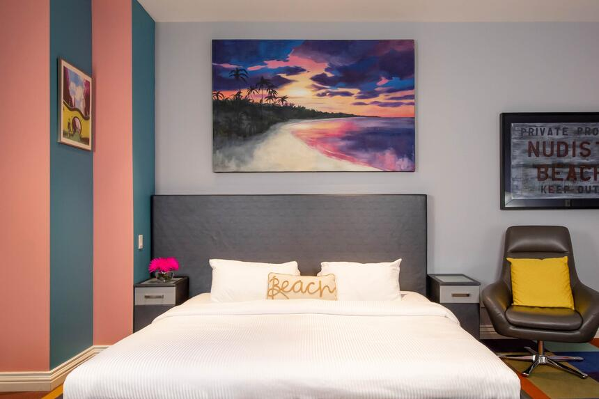 king bed with accent pillow that says beach with sunset artwork