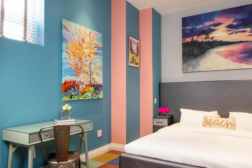 king bed with desk and chair beside, blue and pink walls