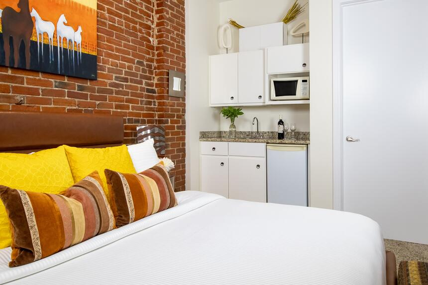 a king bed near a kitchenette with microwave and mini fridge