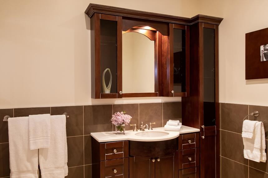 bathroom with built in wooden cabinet with sink and mirror