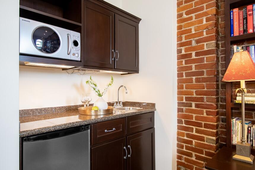 a kitchenette with sink, microwave and fridge near exposed brick