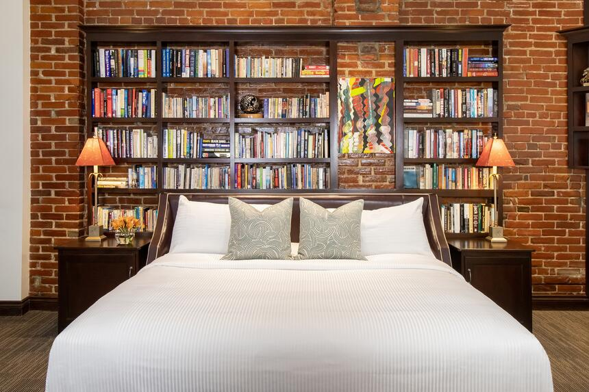 king bed with book collection in behind and bench at foot of bed