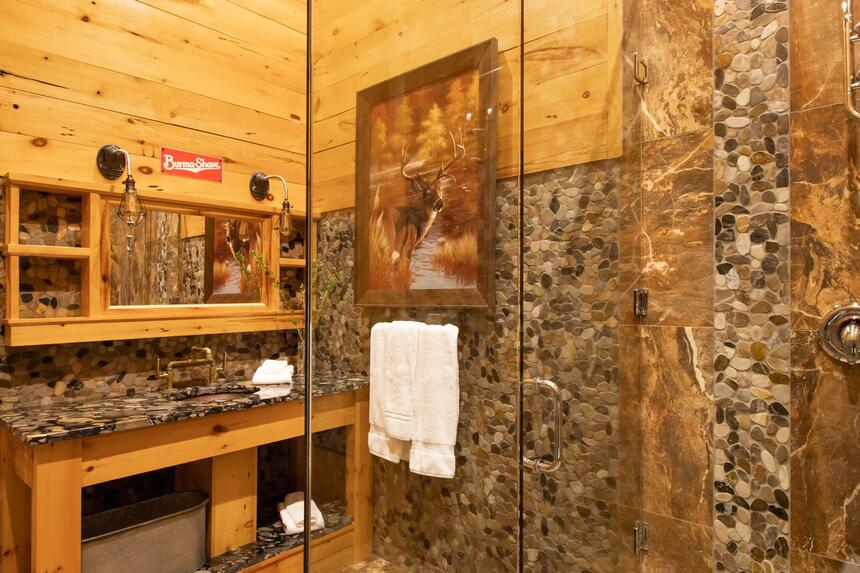glass walk in stone shower in log cabin suite