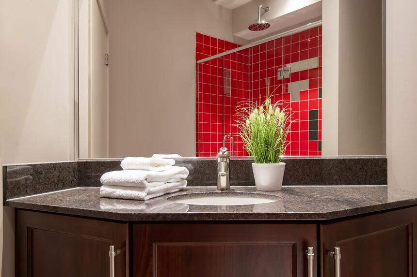 a sink is the focus with folded towels and you can see a bright