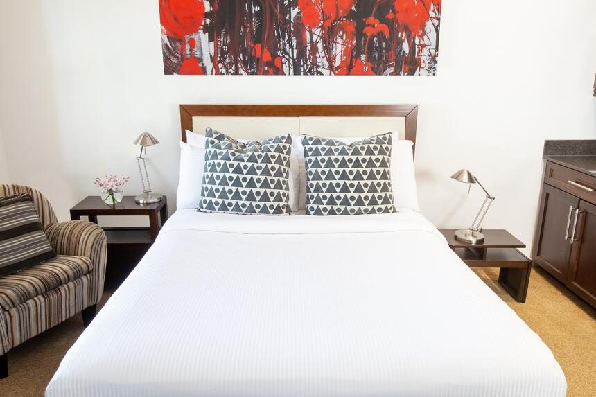 a queen bed in the ruby red suite at retro suites hotel with red