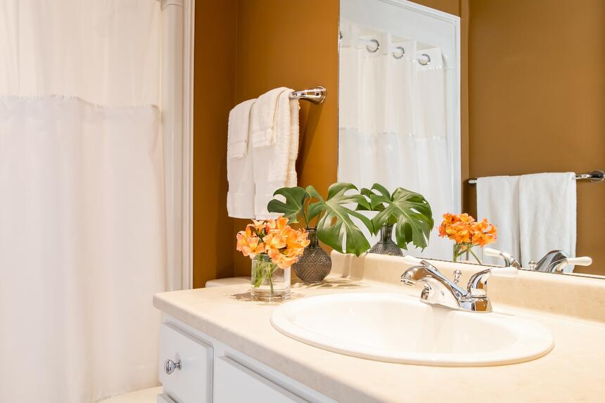 a bathroom sink in front of the mirror with a vase of flowers